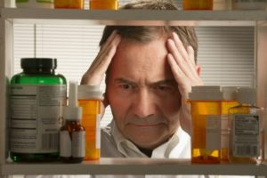 Pharmacist distraught looking at pill bottles