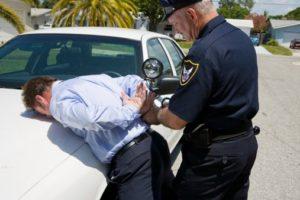 Man on hood of police car