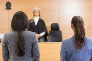 Two people standing in front of a Judge
